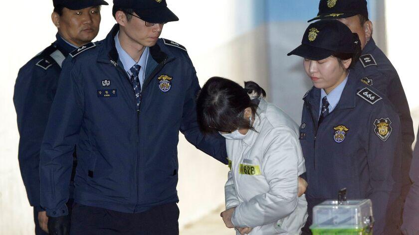 Choi Soon-sil, center, South Korean President Park Geun-hye's longtime friend, arrives for her trial at the Seoul Central District Court in Seoul on Jan. 11, 2017.