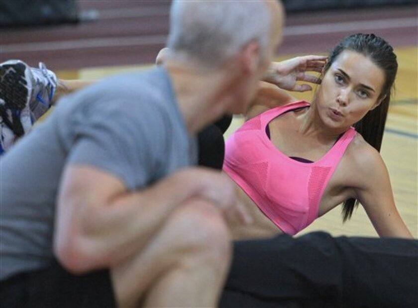 This photo taken Nov. 11, 2009 shows Alicia Hall, right, listens  to instructions from celebrity trainer David Kirsch during a workout session for finalists in the Angel Boot Camp, a model search for Victoria's Secret, New York.  (AP Photo/Bebeto Matthews)