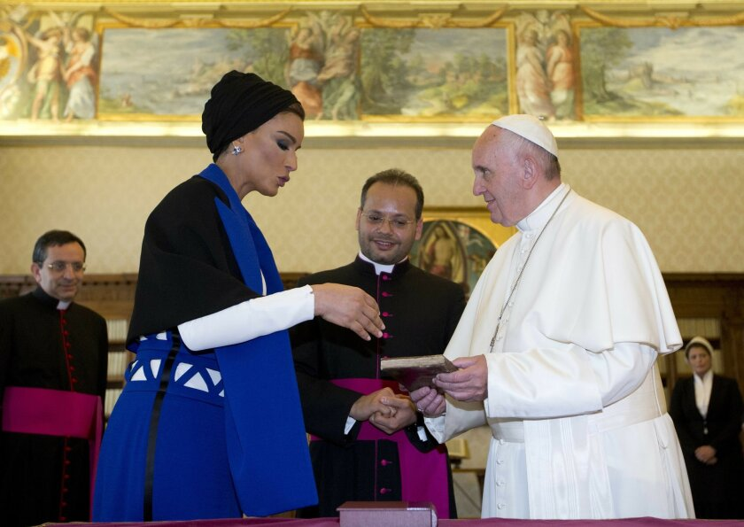 Pope Francis and Qatar's Sheikha Mozah bint Nasser exchange gifts during a private audience at the Vatican, Saturday, June 4, 2016. (AP Photo/Alessandra Tarantino, Pool)