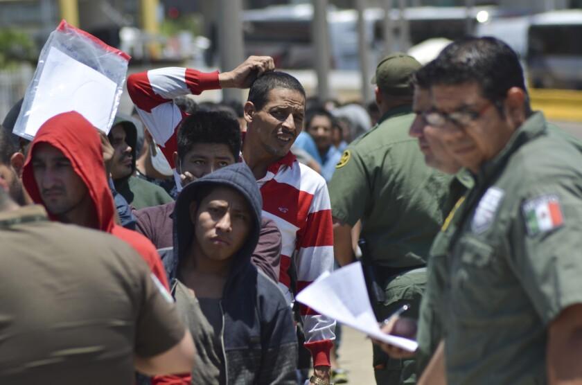 Agentes mexicanos verifican una lista de migrantes devueltos por la Patrulla Fronteriza a México en Nuevo Laredo, estado de Tamaulipas, el jueves 25 de julio de 2019. (AP Foto/Salvador González)