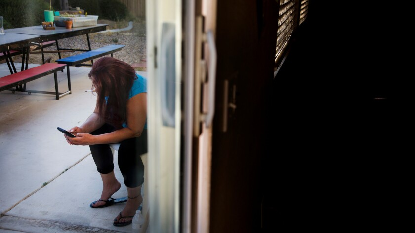 A client of Azalea Springs transitional home takes a cigarette break in the backyard in Hesperia, Calif.