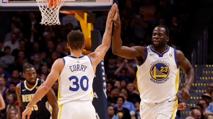 Forward Draymond Green high fives Stephen Curry after Curry hit a three pointer against the Denver Nuggets during the third quarter.