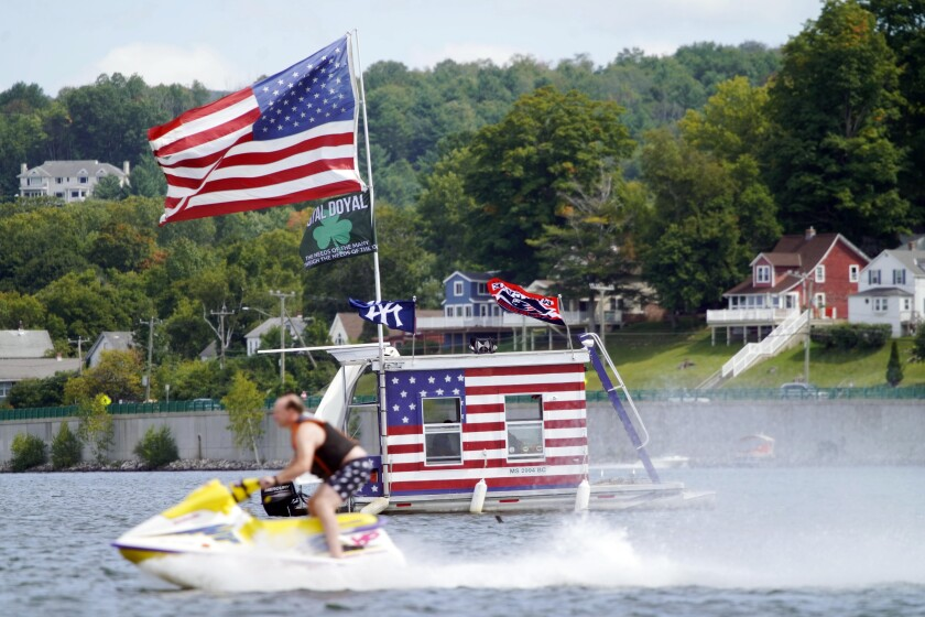 A jet skier passes a patriotic boat owned by AJ Crea on Pontoosuc Lake on Labor Day in Pittsfield, Mass., on Monday.