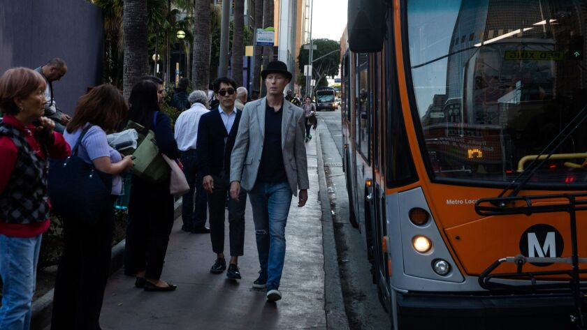 LOS ANGELES, CALIF. - MAY 17: People wait in line at a bus stop near Pershing Square in downtown Los