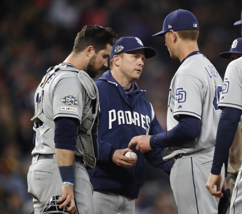 Padres manager Andy Green, center, takes the ball from starting pitcher Eric Lauer, right, as catcher Austin Hedges waits during the fourth inning of Friday's game against the Colorado Rockies.
