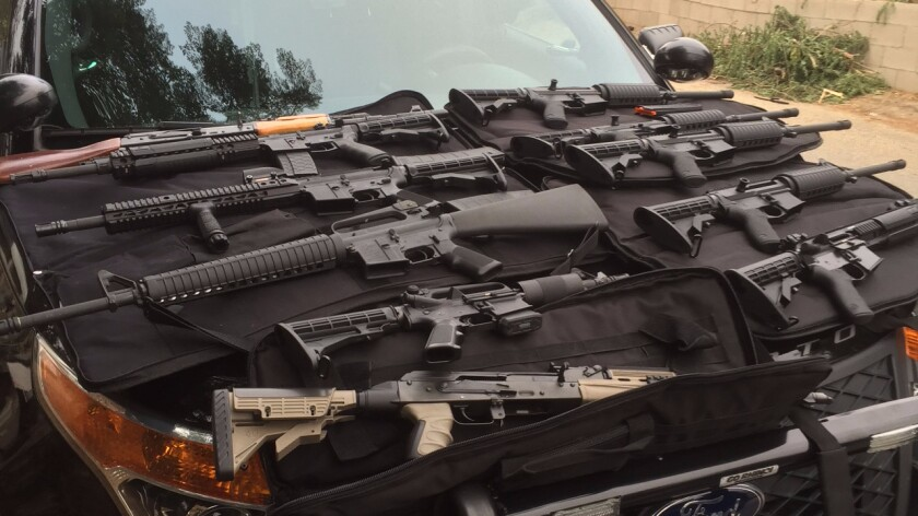 Sixty-seven firearms, including assault rifles and semi-automatic weapons, along with cash and drugs, were seized in a gang sweep in Corona on Thursday.