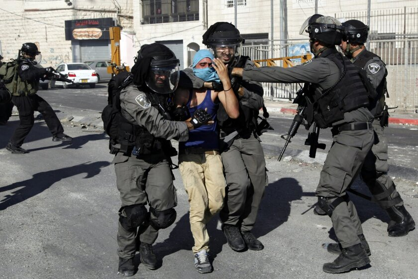 Israeli police officers detain a Palestinian youth during clashes in the Shuafat refugee camp in east Jerusalem, Friday, Sept. 18, 2015. Palestinian protesters continued clashing with Israeli security forces on Friday in various parts of the West Bank and east Jerusalem. Israeli troops fired tear gas, stun grenades and deployed a water cannon to disperse stone-throwing Palestinian youths. Friday's clashes follow days of unrest at Jerusalem's hilltop compound known to the Muslims as the Noble Sanctuary and to Jews as the Temple Mount (AP Photo/Mahmoud Illean)