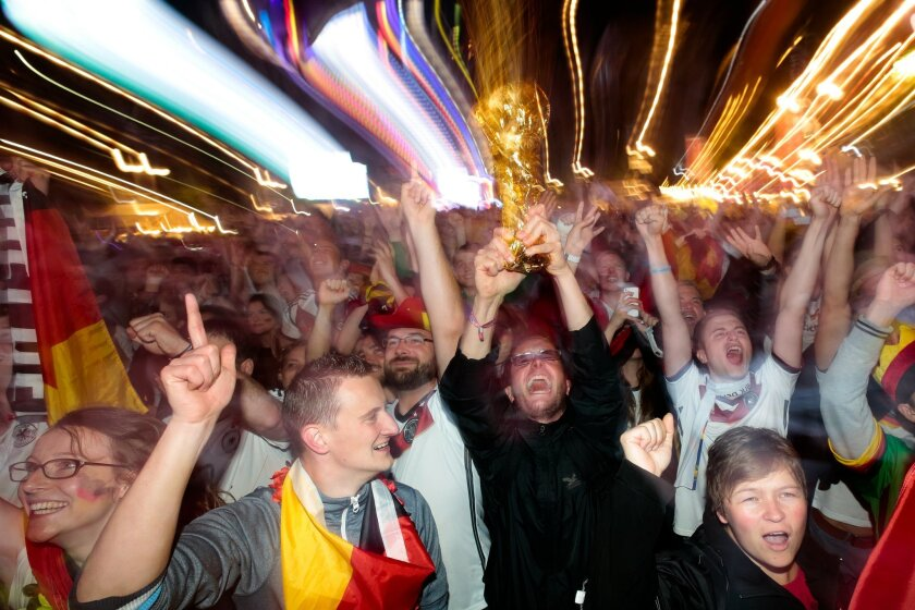 In this photo taken with a long shutter, German fans celebrate their team after Germany won against Argentina by 1-0 at the soccer World Cup final in Rio de Janeiro, Brazil, at a public viewing area called 'Fan Mile' in Berlin, Sunday, July 13, 2014. (AP Photo/Markus Schreiber)
