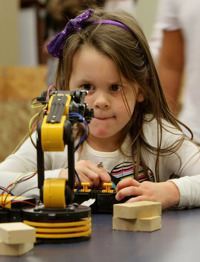 Four-year-old Mila McDuffie uses controls to direct a robot to stack blocks of wood at the 4th Annual Robots Expo at CSU San Marcos. Her father, Michael McDuffie, is a philosophy professor at the school.