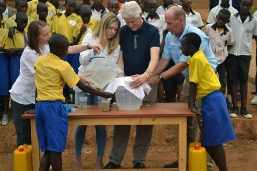 President Clinton and daughter Chelsea, middle, gesture after purifying a bucket of dirty water to safe drinking water Monday Aug. 5, 2013 at Group Scolaire Camp Kanombe outside the capital Kigali. President Clinton was on a two-day visit to the central African country as part of his African tour which took him to Malawi and South Africa. Looking on is Dr Greg Alllgood of World Vision, second right, and Allison Tummon Kamphuis , second left,from Proctor & Gamble as well as school children from r