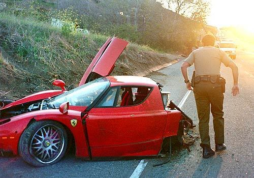 A deputy passes the wrecked Ferrari that crashed on Pacific Coast Highway west of Decker Canyon Road. The car's registered owner, Swedish millionaire Stefan Eriksson, said that he was a passenger. On Monday, he was charged with grand theft, embezzelment and a firearms violation.