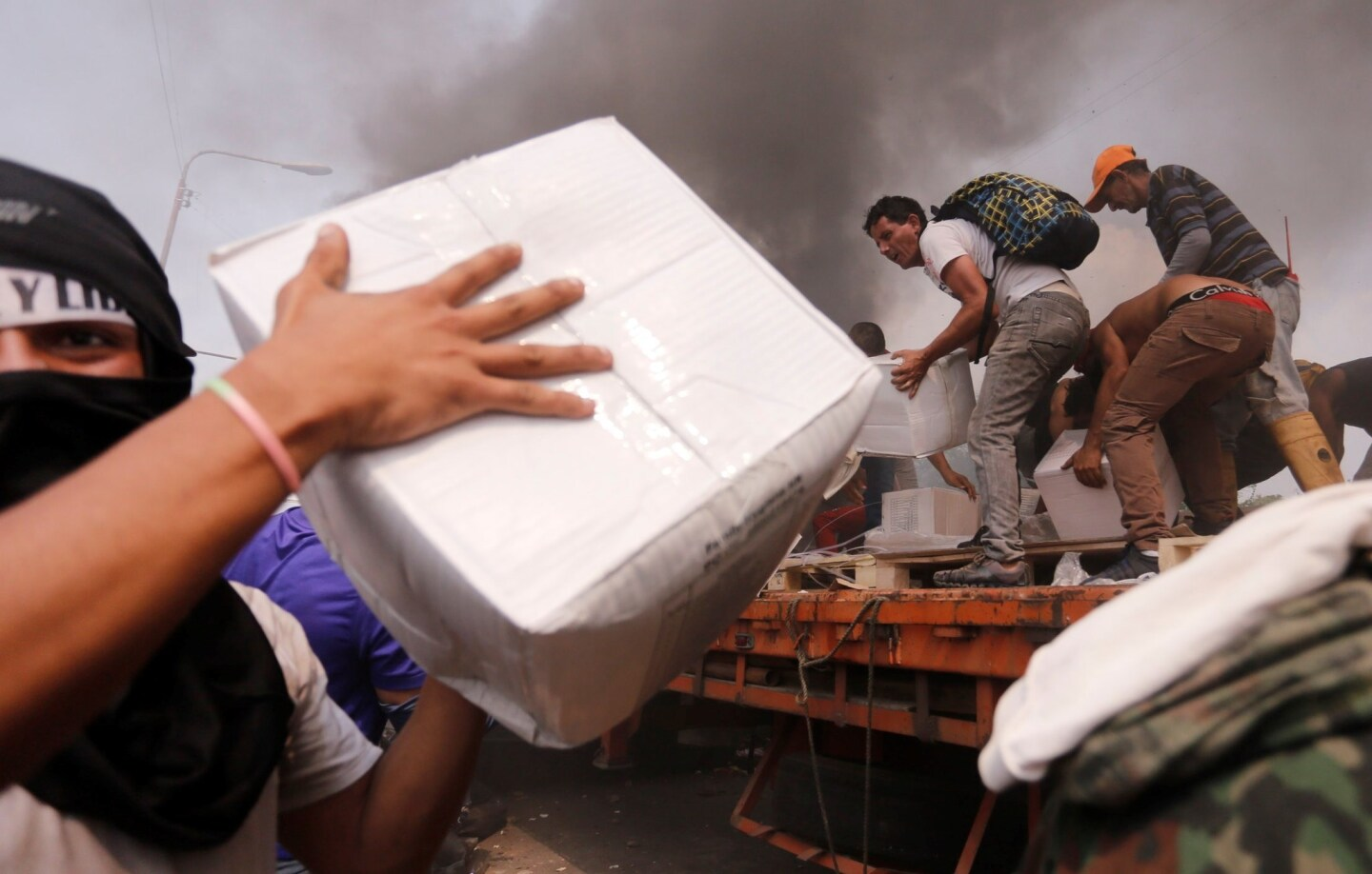 People try to take part of the humanitarian aid from a truck that was set on fire in Urena, Venezuela, on Saturday. Two trucks with aid requested by the opposition were burned by Venezuelan security forces at a border bridge with Colombia.