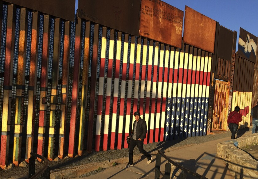 People walk past a mural of an upside down U.S. flag painted on the border fence