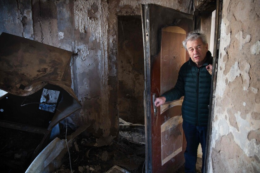 Israeli Aitan Shariel inspects the damage inside his house in the northern city of Haifa following a wildfire which authorities say was deliberately set.