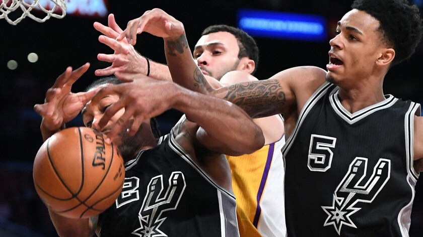 Spurs forward Kawhi Leonard and Dejounte Murray battle for a rebound against Lakers forward Larry Nance Jr. in the fourth quarter.
