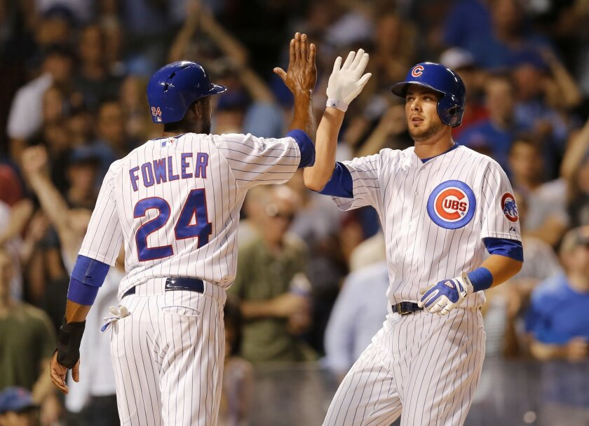 Chicago Cubs' Kris Bryant, right, celebrates with Dexter Fowler after the pair scored on Bryant's two-run home run off Los Angeles Dodgers starting pitcher Clayton Kershaw, during the third inning of a baseball game Monday, June 22, 2015, in Chicago. (AP Photo/Charles Rex Arbogast)