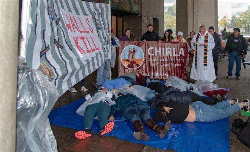 """Fotografía cedida por la Coalición por los Derechos Humanos de los Inmigrantes (CHIRLA) donde aparecen varios jóvenes tumbados en el suelo debajo de un eslogan que lee en inglés """"las paredes matan"""", durante una protesta de un grupo de unos 40 activistas hoy en Los Ángeles contra el acuerdo legislativo federal que destina dinero a la construcción de un muro en la frontera entre Estados Unidos y México. EFE/CHIRLA/SOLO USO EDITORIAL/NO VENTAS"""