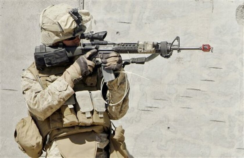 Marine Pfc.Jesse Young, 19, of Clinton, Conn., wearing body armor, surveys the terrain through his weapon's sight after entering a mock village during a training exercise Tuesday, Sept. 23, 2008, at the Marine Corps Air Ground Combat Center in Twentynine Palms, Calif.  Acting on widespread complain