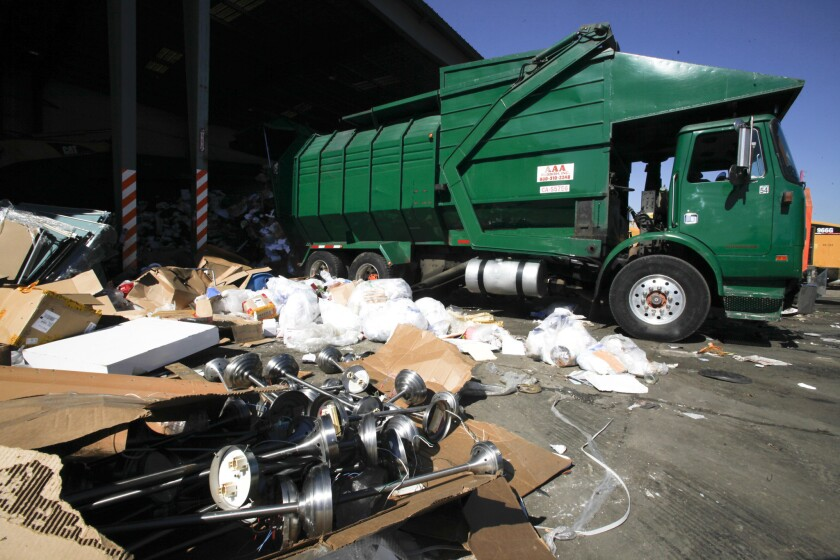 A truck with AAA Rubbish Inc. backs into a dumping spot at City Terrace Recycling in 2012.