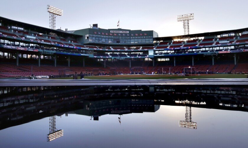 FILE - In this Oct. 21, 2018, file photo, Fenway Park is reflected in a puddle on the roof of the visitors' bullpen at dusk as the Houston Astros work out in Boston. One of two men charged with repeatedly raping a teenage boy at New Hampshire's youth detention center in the late 1990s went on to work as a clubhouse attendant for the Boston Red Sox, which suspended him when it learned of the allegations, the team told The Associated Press on Monday Jan. 6, 2020. (AP Photo/Charles Krupa, File)