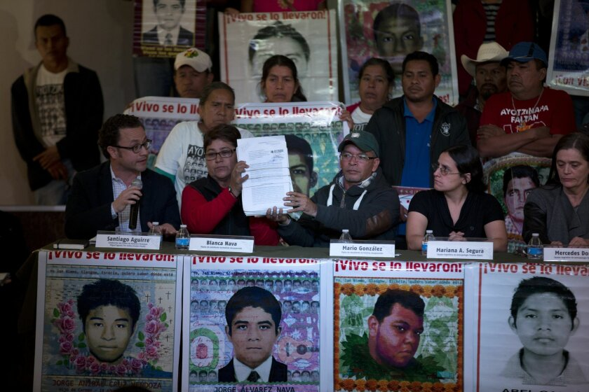 Blanca Nava, second left, and Mario Gonzalez, third left, both relatives of missing students, hold up a copy of an investigation that an Argentine Forensic Anthropology Team gave to the Mexican Attorney General's Office, during a news conference in Mexico City, Tuesday Feb. 9, 2016. The team announ