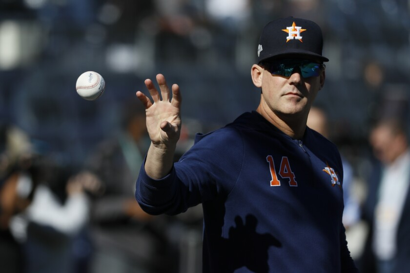Houston Astros manager AJ Hinch catches a ball before a playoff game in 2019.