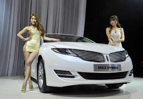 """South Korean models pose with the all-new Lincoln MKZ Hybrid at the Seoul Motor Show last month. KBB says, """"Lincoln's gas/electric mid-size sedan is as contemporary a vehicle we've seen from the automaker in a long time."""" City/highway/combined mpg: 45/45/45. MSRP: $36,800."""