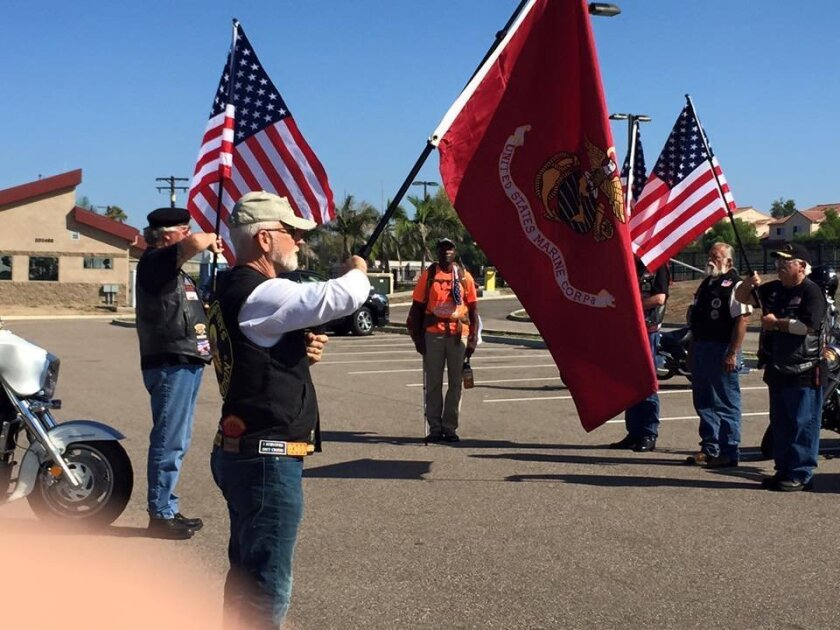 Retired Gunnery Sgt. Roy Brady, Jr. gets a flag salute from veterans as he arrives at Camp Pendleton after a 3,000 mile cross country trek to raise money for the Combat Wounded Veteran Challenge.