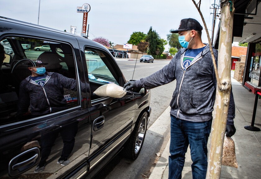 David Fuerte of Masataco in Whittier delivers bags of rice and beans to a customer during the coronavirus pandemic on March 31. Fuerte converted his vegan Mexican restaurant into a curbside, drive-up operation and recently adding medical-grade face masks to the menu.
