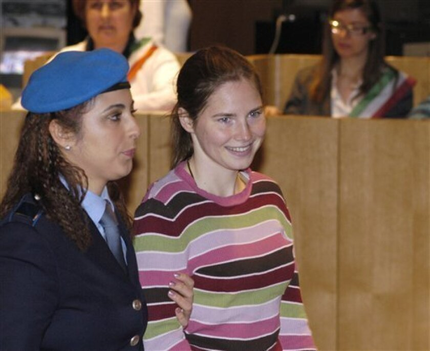 US murder suspect Amanda Knox, right, is escorted in a courtroom during a hearing, in Perugia, Italy, Friday, March 13, 2009. Knox, and Knox's former Italian boyfriend, Raffaele Sollecito, are being tried on charges of sexual violence and murder of her British roommate Meredith Kercher in Perugia l