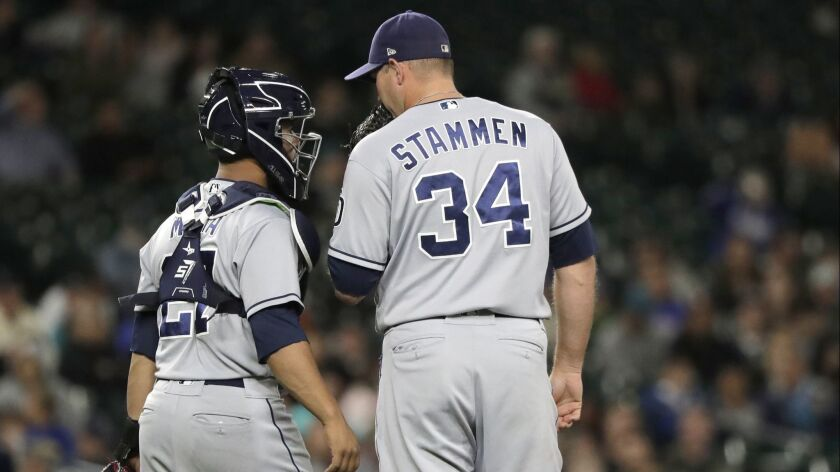 Craig Stammen talks with catcher Francisco Mejia during the eighth inning Tuesday night in Seattle.
