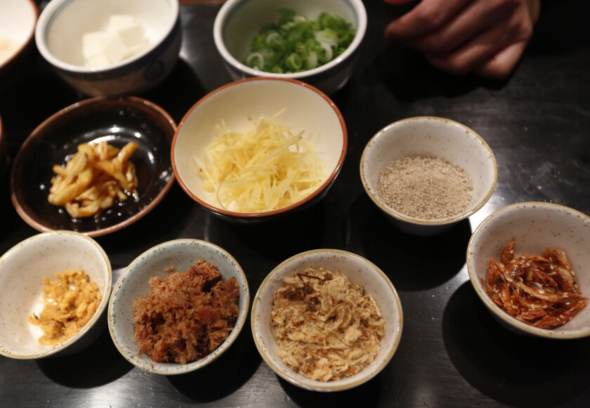 Some of the different items that will go into a seafood congee are lined up on the counter prior to