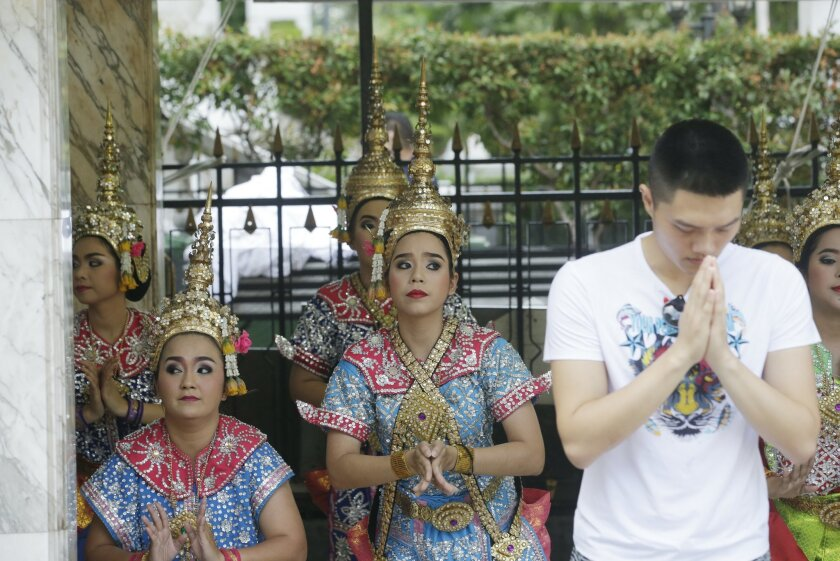 A visitor prays as Thai classical dancers perform at the Erawan Shrine at Rajprasong intersection, the scene of Monday's bombing, in Bangkok, Thailand, Friday, Aug. 21, 2015. Religious ceremonies were held to honor the victims of the deadly bombing at a Bangkok shrine four days ago. (AP Photo/Sakchai Lalit)