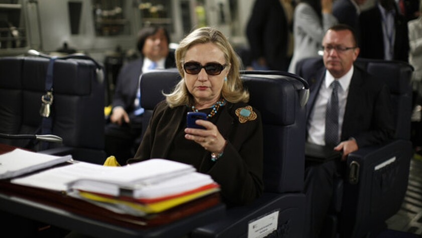 Hillary Clinton checks out her smartphone during a trip while serving as secretary of State.