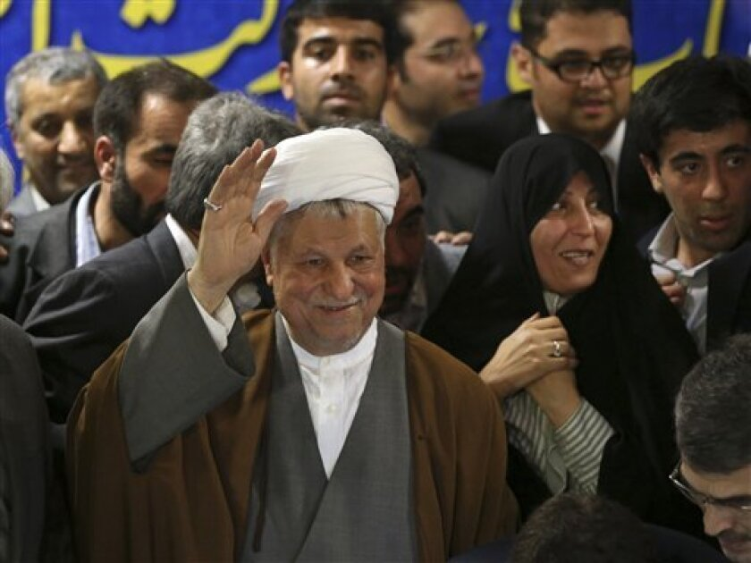 In this Saturday, May 11, 2013 photo, former President Akbar Hashemi Rafsanjani, waves to media, as he registers his candidacy for the upcoming presidential election, while his daughter Fatemeh, smiles at second right, at the election headquarters of the interior ministry in Tehran, Iran. On Saturday Rafsanjani's made a last minute surprise decision to enter Iran's presidential election process, which now includes more than 680 hopefuls and will culminate June 14 with just a handful of names on