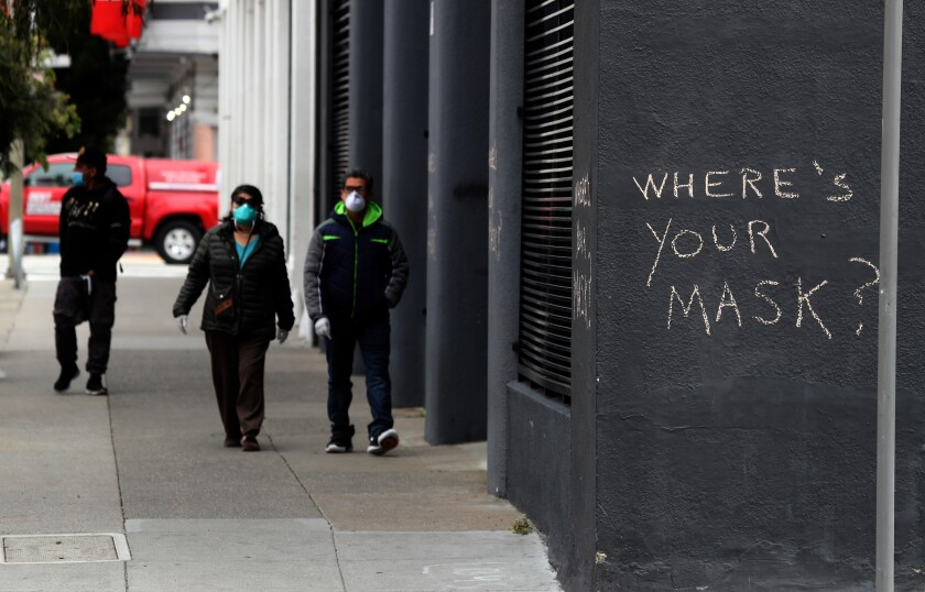 Pedestrians walk by graffiti encouraging the wearing of masks on April 20, 2020 in San Francisco.