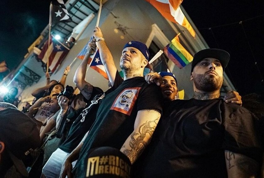 Residente (centro) y Nicky Jam durante una manifestación previa a la renuncia de Rosselló.