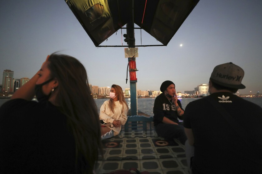 From left to right, April Joy, vocalist, Catherine Gallano, dancer and lead choreographer and Eric Roman, vocalist, cross the creek on a boat in Dubai, United Arab Emirates, Wednesday, Oct. 28, 2020. As the coronavirus pandemic mutes Dubai's live-music scene, the Filipino show bands that long have animated the city's storied nightlife are being disproportionately squeezed. Many are out of work and out of money, struggling to survive in overcrowded dormitories at the mercy of employers (AP Photo/Kamran Jebreili)