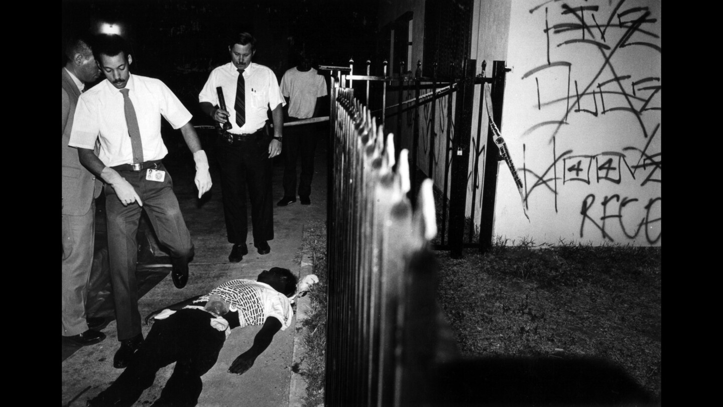 A coroner's team prepares to examine the body of a gang member killed in a drive-by shooting on 42nd Place. Five Deuce Hoover Crips graffiti can be seen crossed out on the wall of the apartment next door.