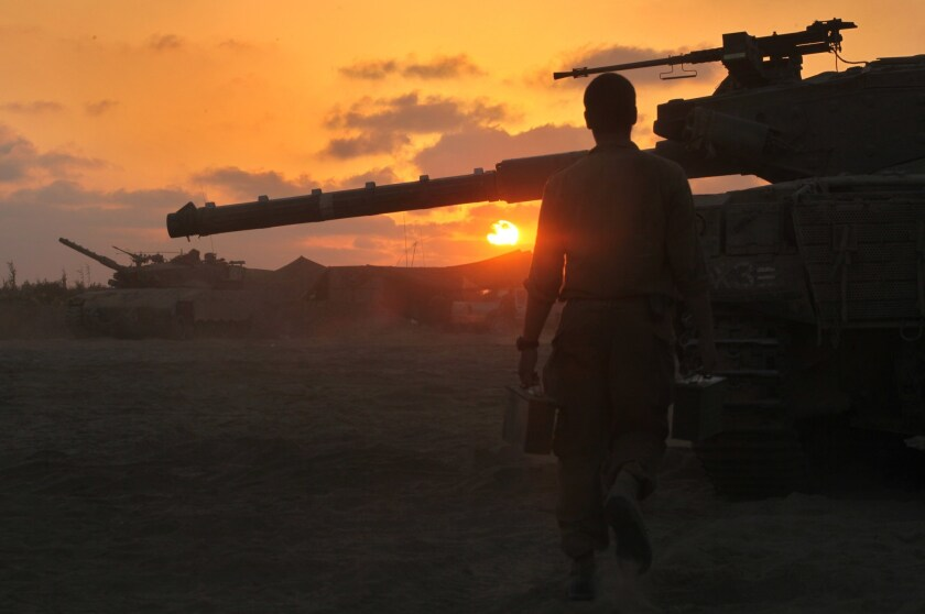 An Israeli soldier walks past a Merkava tank along the border between Israel and the Hamas-controlled Gaza Strip after returning from combat in the Palestinian enclave.