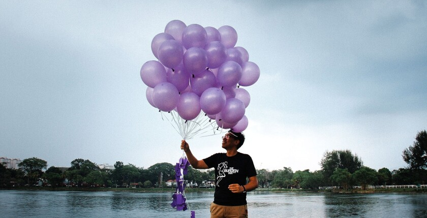 A volunteer from a nongovernmental organization called Malaysians for Malaysia gets ready to release balloons in Kuala Lumpur in honor of the passengers and crew aboard missing Malaysia Airlines Flight 370.