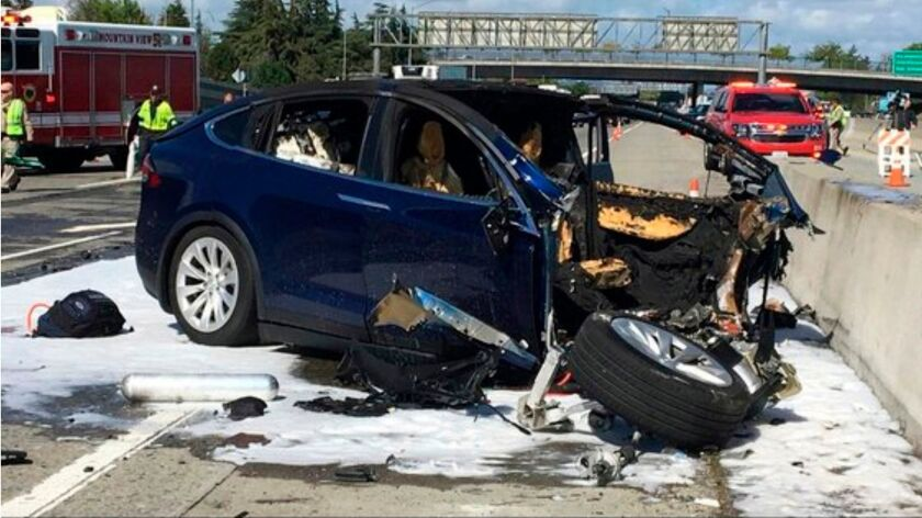 Emergency personnel work at the scene where a Tesla SUV crashed into a barrier on Highway 101 in Mountain View, Calif. The National Transportation Safety Board is investigating.