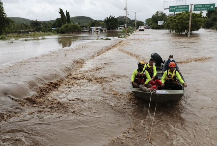 Rescuers navigate a flooded road in a boat after Hurricane Iota passed through La Lima, Honduras.