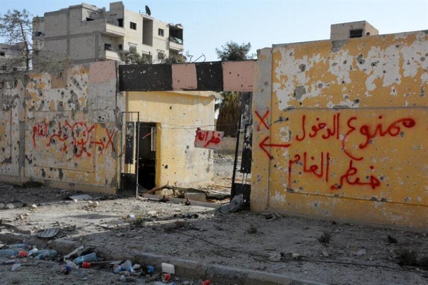 Un muro con pintadas en las que se prohíbe la entrada por riesgo de minas en árabe, en medio de la ciudad destruida de Al Raqa. EFE/Archivo