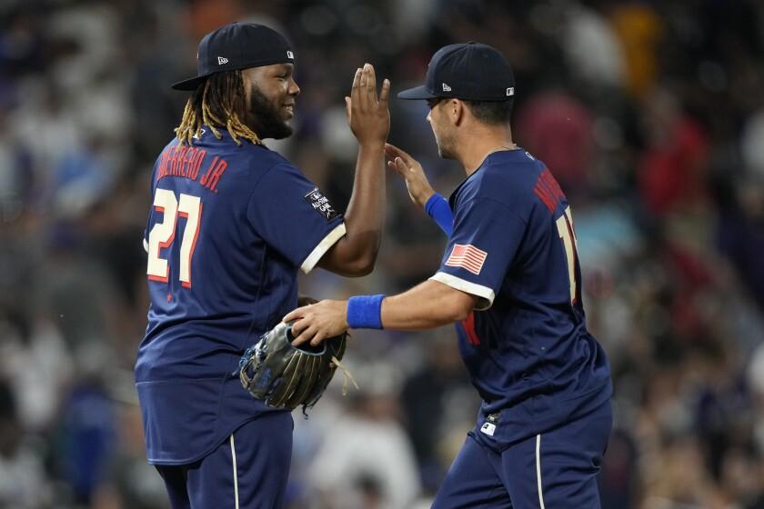 American League's Vladimir Guerrero Jr. greets Whit Merrifield.