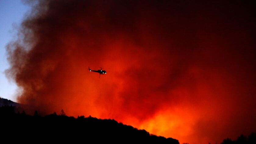 SANTA ROSA, CA -- OCTOBER 14, 2017 -- A helicopter prepares to drop water on a fire that threatens t