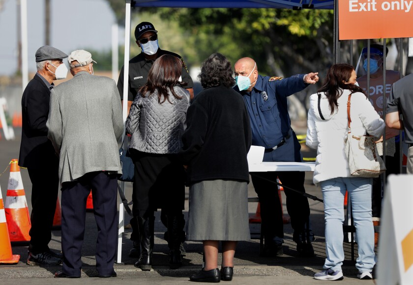 People line up at a checkpoint to be vaccinated at W. 79th Street and S. Mariposa Avenue in South Los Angeles on Tuesday.