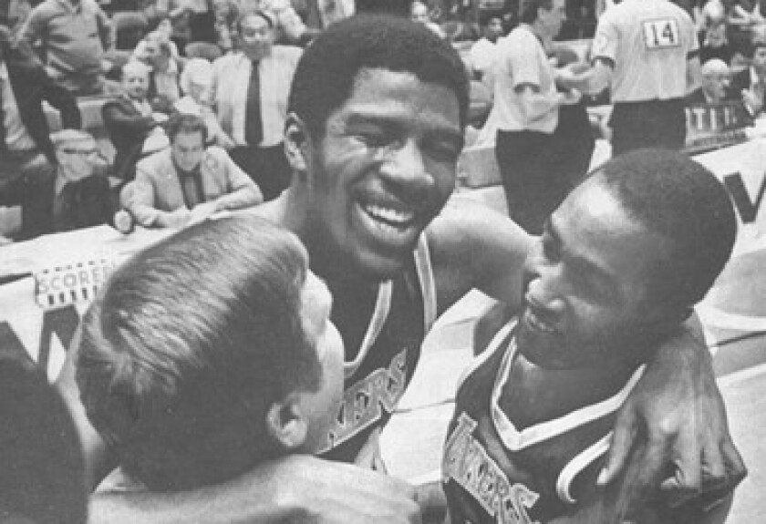 Magic Johnson, center, is embraced by trainer Jack Curran and teammate Butch Lee after the Lakers defeated the 76ers to win the 1980 NBA title.