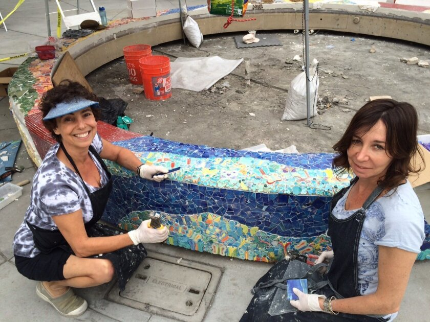 Helen Segal and Barbi Dorfan work on a new mosaic fountain at Torrey Hills Shopping Center. Photo by Karen Billing