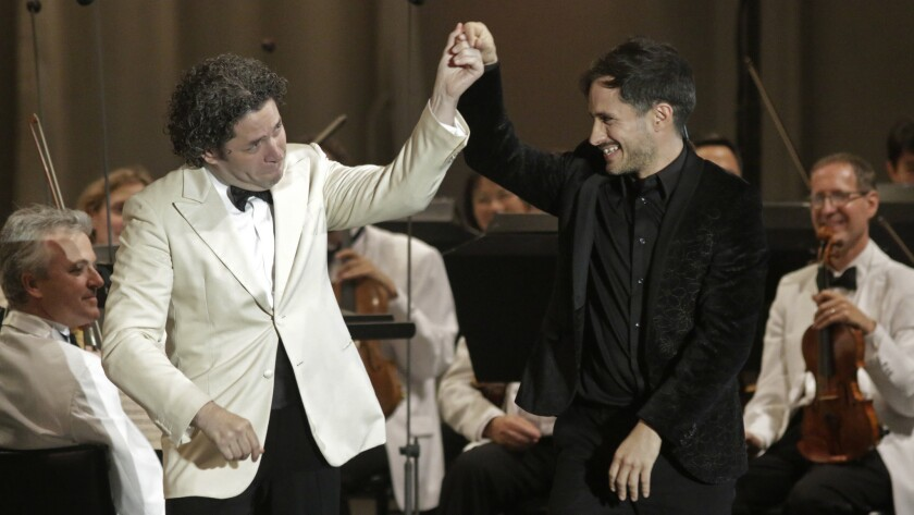 """Gustavo Dudamel, left, gives a nod to Gael García Bernal after the actor's """"guest conducting"""" in a performance at the Bowl."""